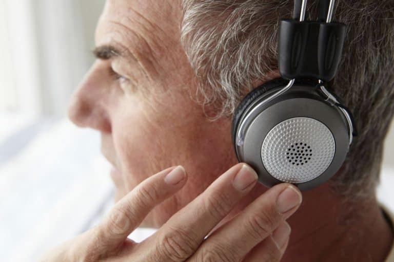 Hombre mayor escuchando con auricular Sony