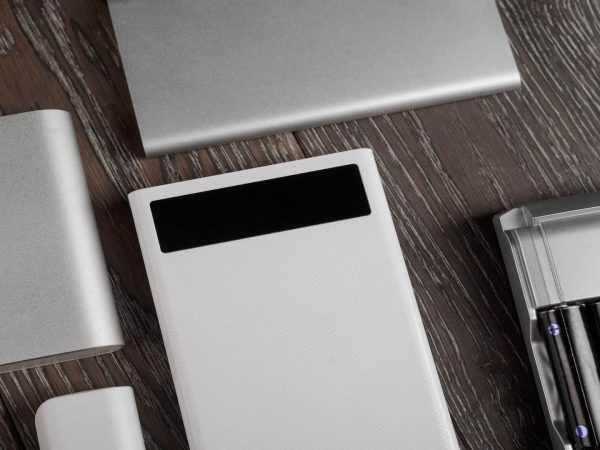 Flat lay of different power banks on wooden table. Various design and specs. Modern charging devices.