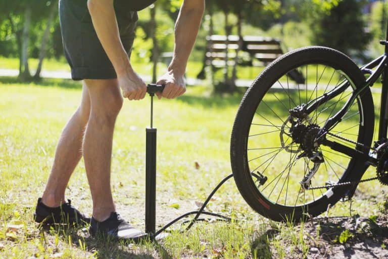 Ciclista llenando de aire llanta de bicicleta