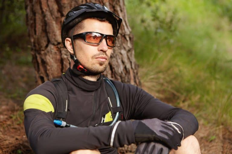 Ciclista descansando en árbol