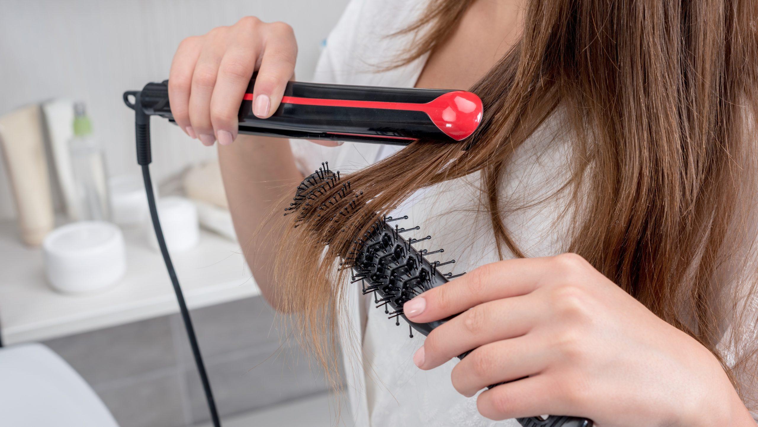 Mujer secando se el cabello con cepillo ionico