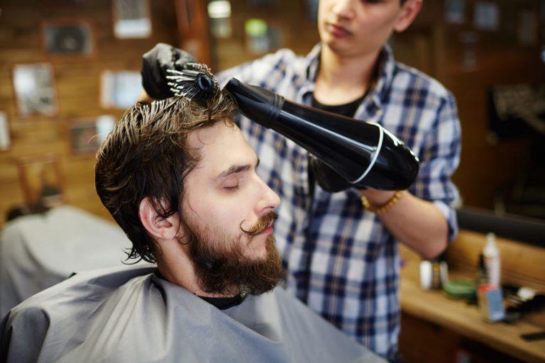 hombre secandose el cabello con secador y cepillo ionico