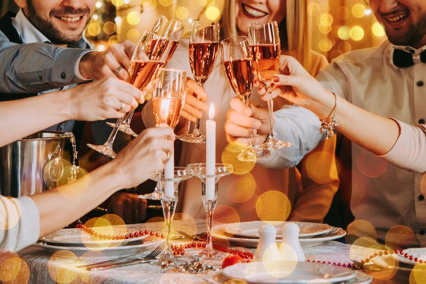 Amigos celebrando la víspera de Navidad o año nuevo. Mesa de fiesta con champagne rosa.