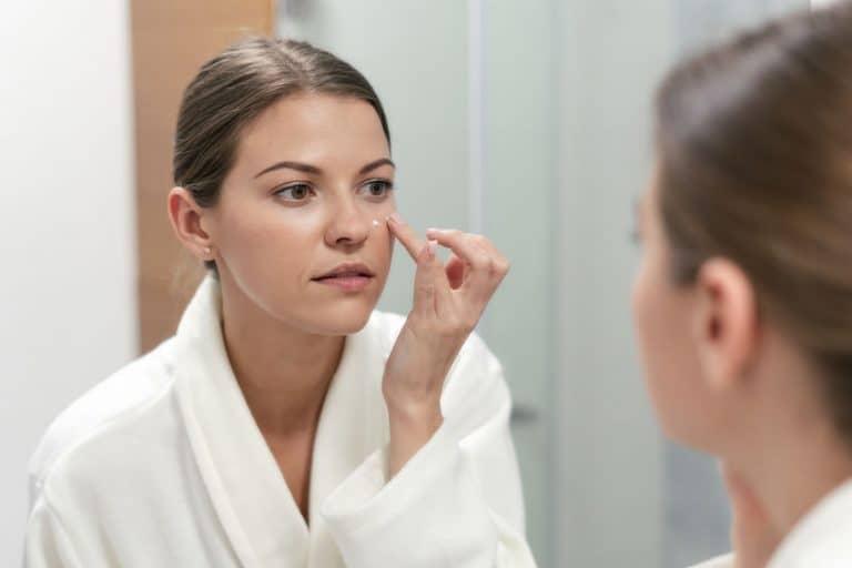 Mujer frente al espejo aplicándose crema