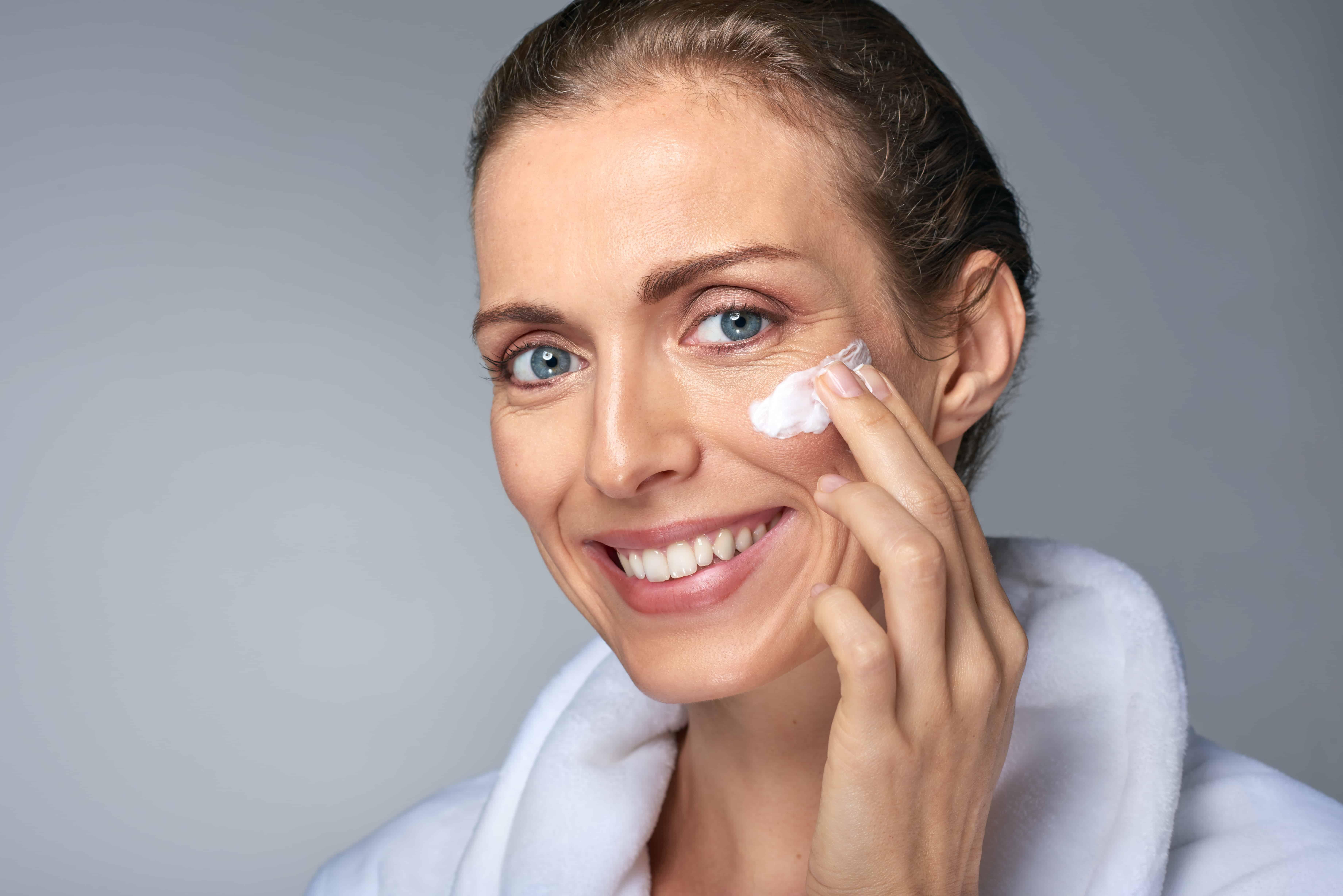 Mujer aplicándose crema en la cara