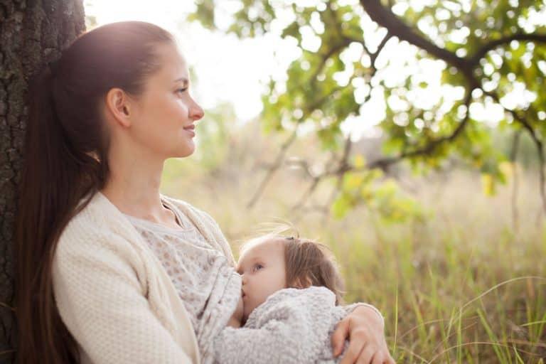 Madre amamantado a sus hijo al aire libre
