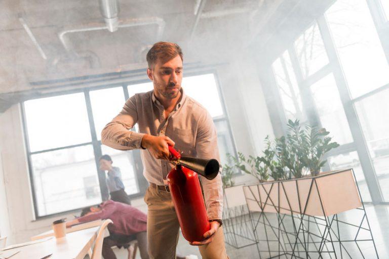 Hombres abiendose paso en incendio con extintor