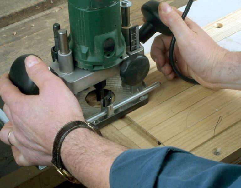Joven haciendo cortes a madera con fresadora color verde