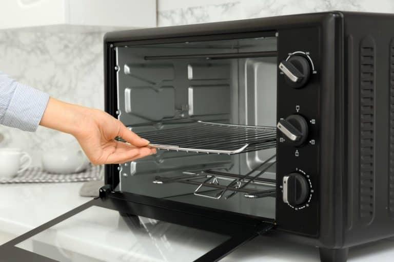 Una persona abriendo un horno de convección