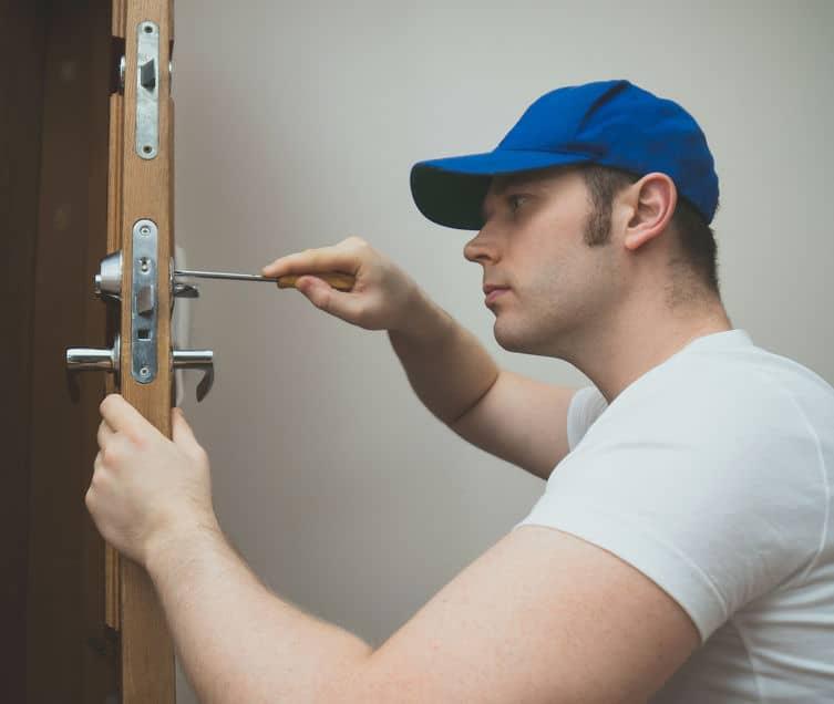 Hombre uilizndo destornillador para reparar puerta