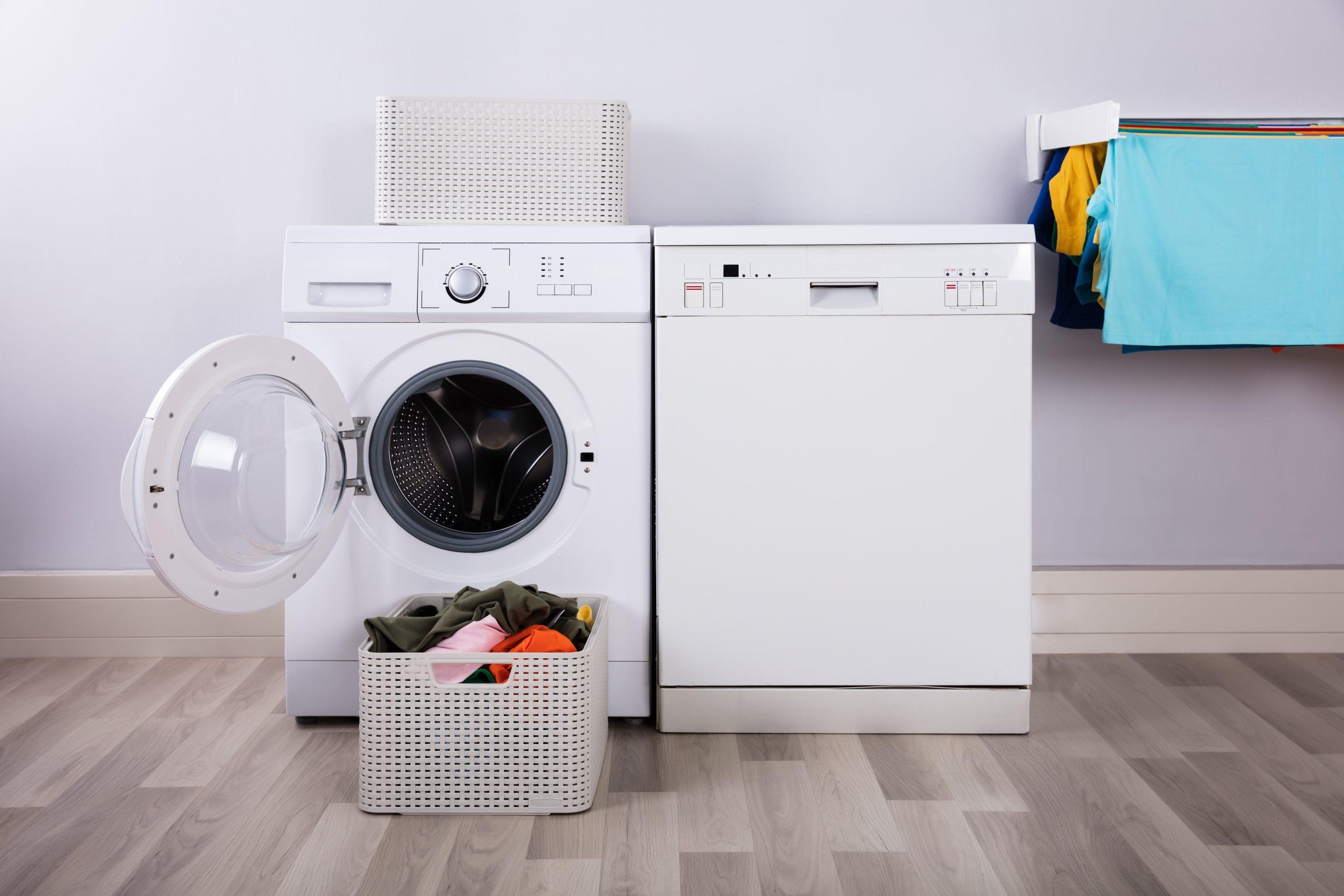 Lavadora junto a canasta de ropa