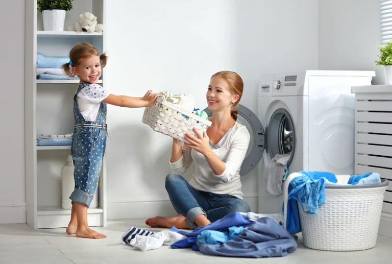 Madre e ija lavando ropa en lavadora