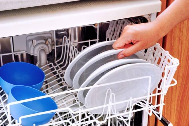 Mujer tomado un plato del lavavajillas