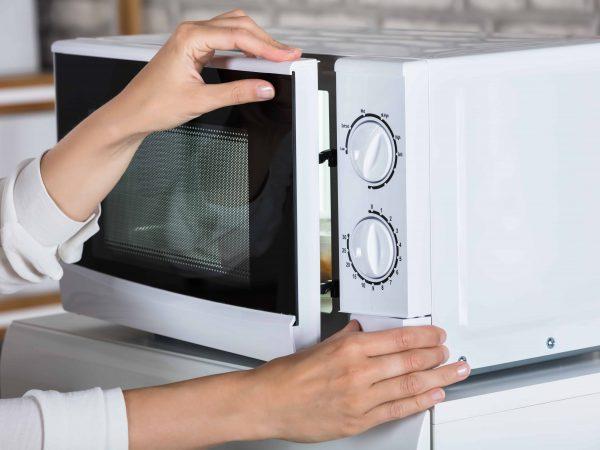 Mujer abriendo puerta de microondas