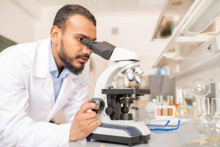 Hombre viendo a traves de microscopio