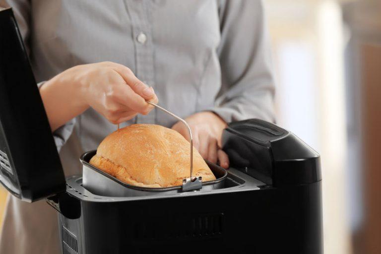 Mujer sacando pan recién hecho de panificadora