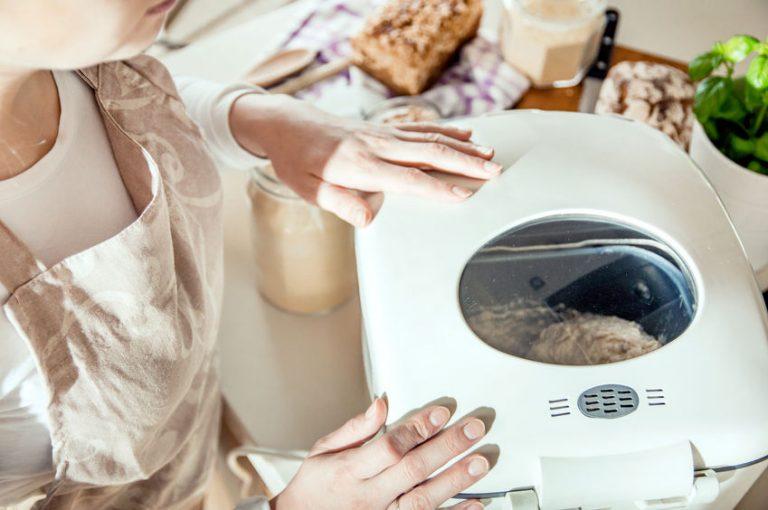 Mujer haciendo pan con panificadora
