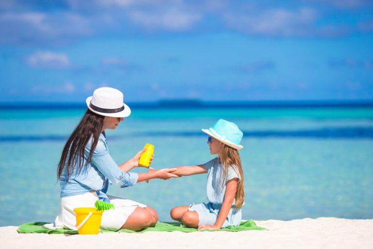 Made e hija en playa aplicándose protector solar