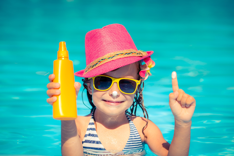 Niña con protector solar en piscina