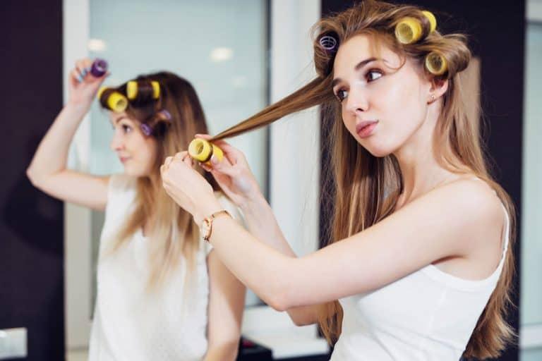 Dos chicas usando rulos para rizar el pelo