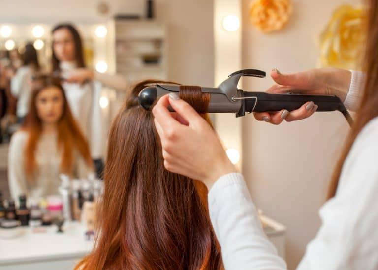 Una peluquera rizando el pelo a una clienta