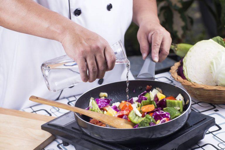 Chef cocinando en sartén para inducción