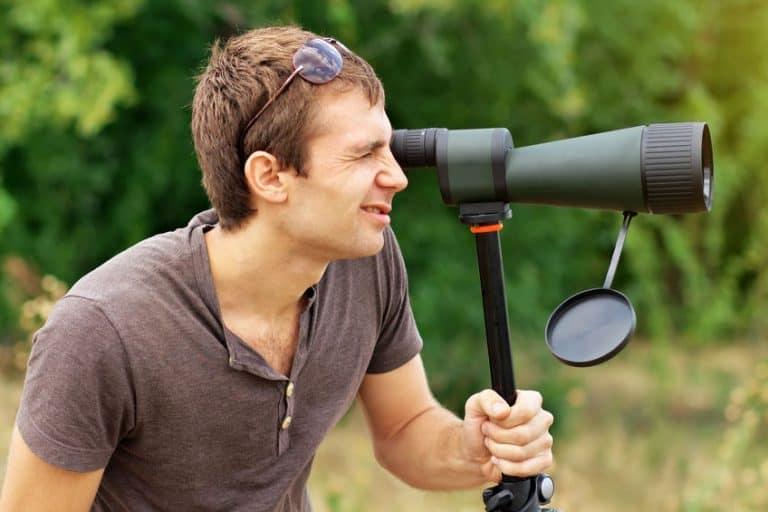 Hombre utilizando telescopio terrestre