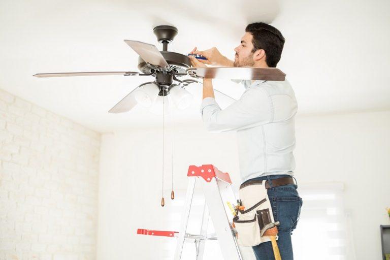 Hombre instalando el ventilador en una escalera