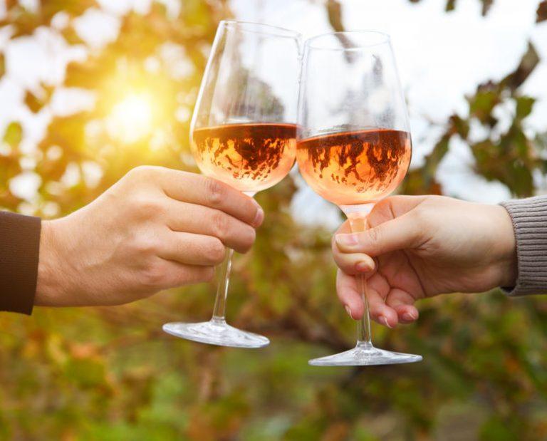Personas brindando con vino rosado