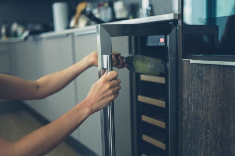 Mujer en la cocina sacando vino de vinoteca