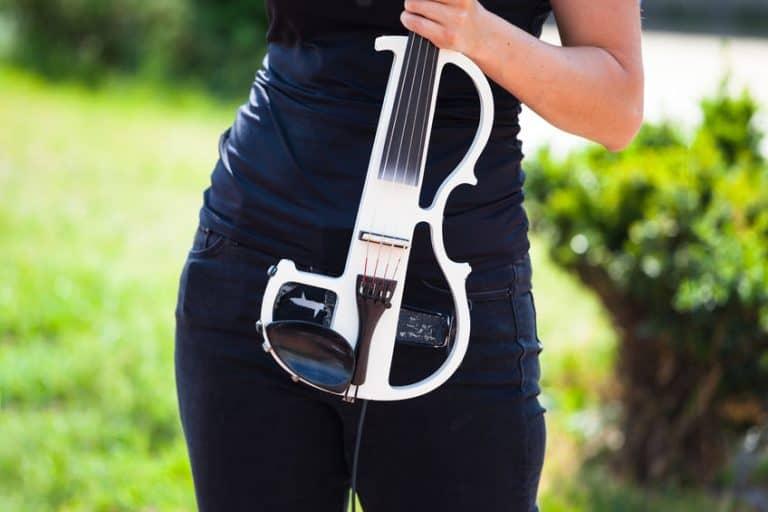 Mujer sosteniendo violín eléctrico
