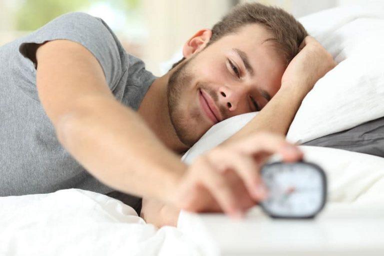 Hombre despertándose con despertador