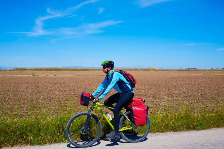 Un hombre pedalendo una bici con alforjas