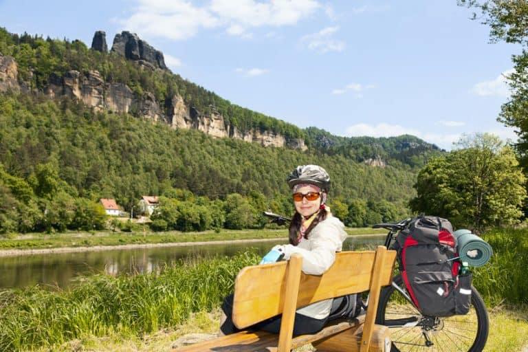 Una mujer de excursión con una bici con alforjas