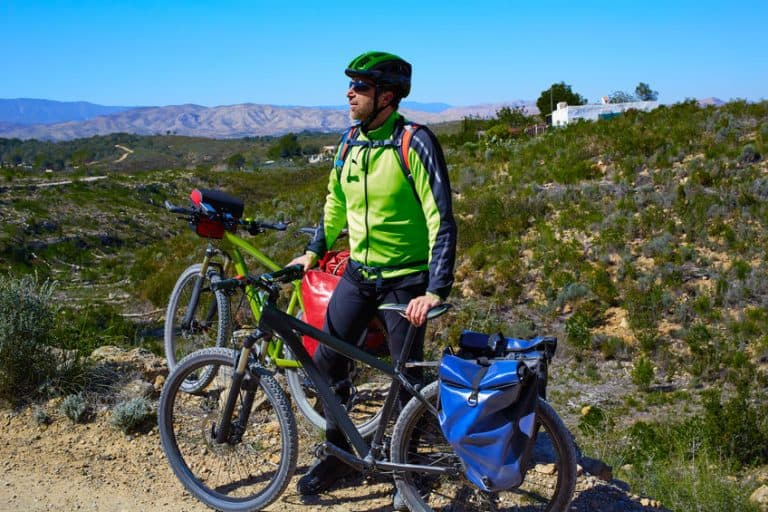 Un hombre junto a una bicicleta con alforjas