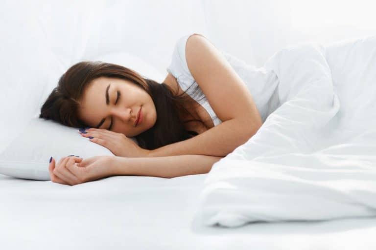 Una mujer durmiendo en la cama con una almohada