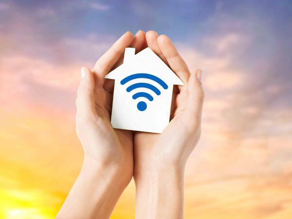 Unas manos sujetando una casita con símbolo de wifi