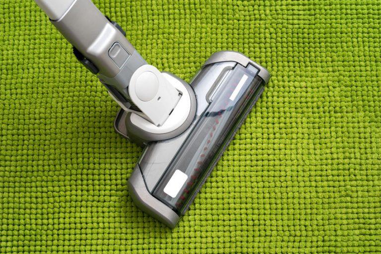 aspirador sobre alfombra verde