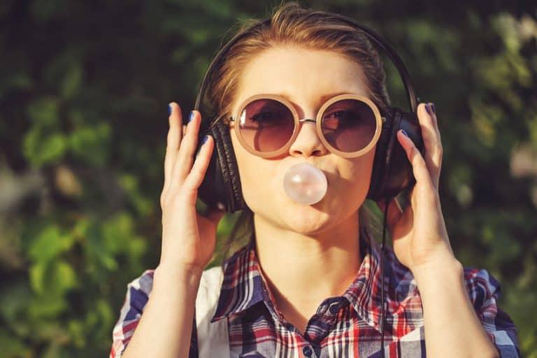 Mujer con audífonos mascando chicle
