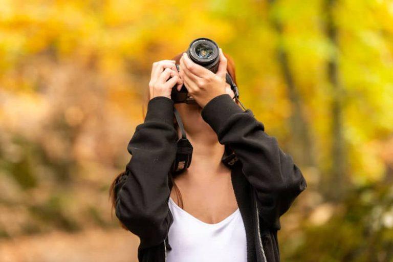Una chica haciendo una foto con una cámara reflex
