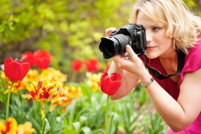 Chica haciendo una foto a varias flores