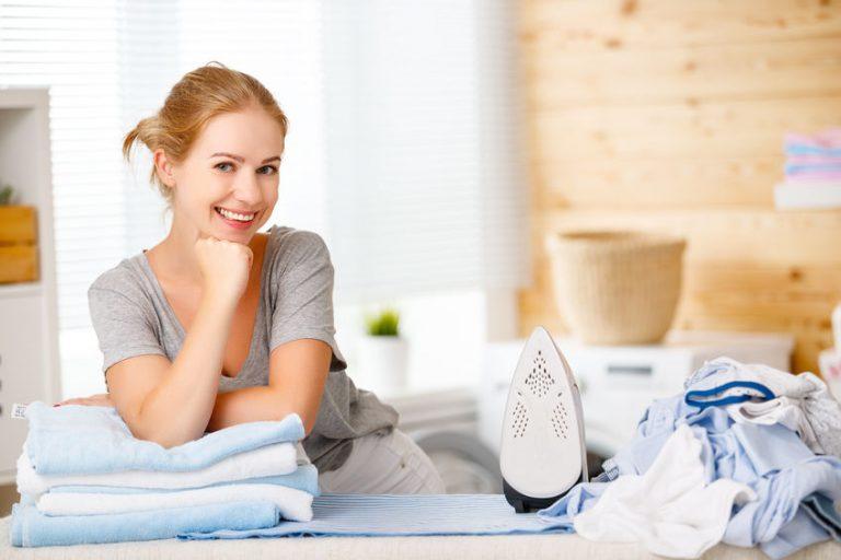 Una mujer rodeada de ropa planchada