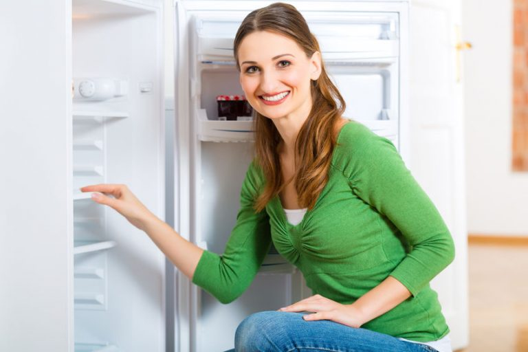 Una mujer enfrente de un congelador
