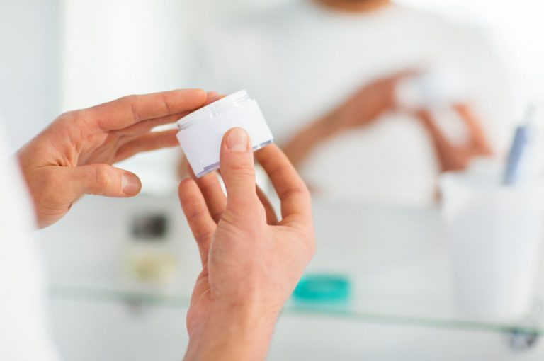 Hombre abriendo frasco de crema