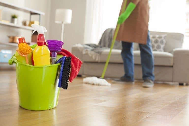 Hombre fregando el parqué con más productos de limpieza