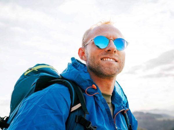Un chico en la montaña con gafas de sol