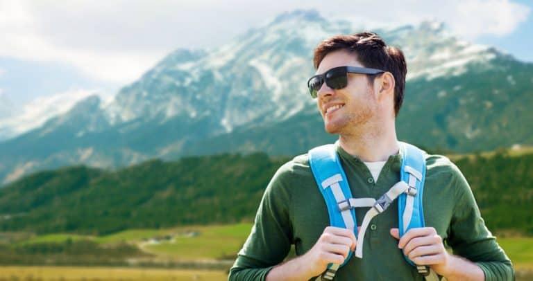 Un chico en una montaña de excursión con gafas de sol