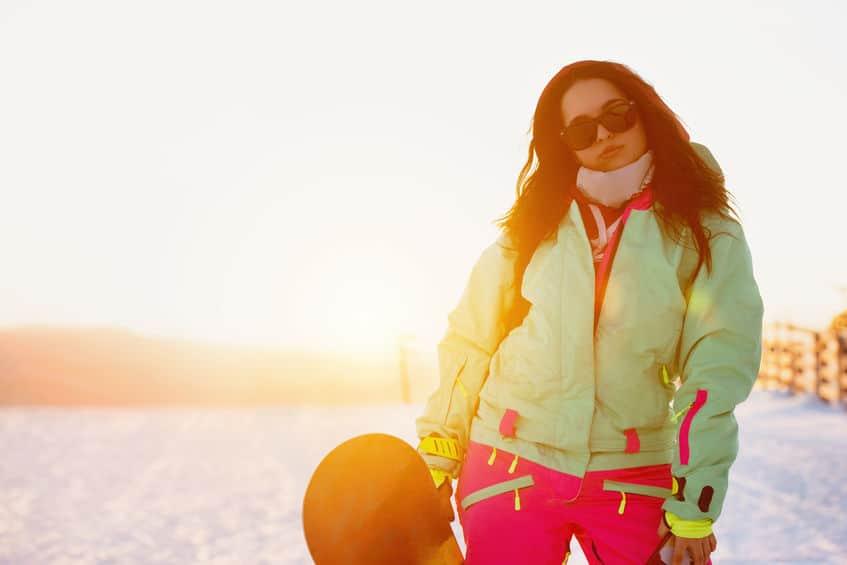 Una chica con un snowboard con gafas de sol