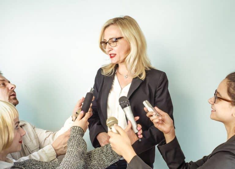 Varios periodistas entrevistando a una mujer