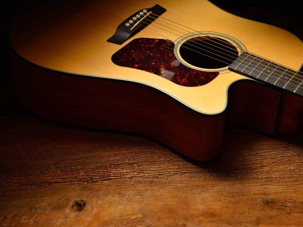 Una guitarra acústica en el suelo de madera